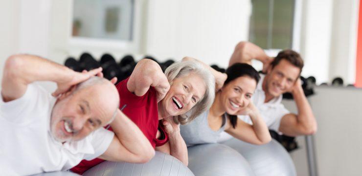 lachende ltere frau trainiert in der gruppe